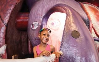 Young girl smiling, walking through The Giant Heart at the Franklin Institute.