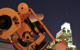 The Franklin Institute's telescope trained on a planet above the Philadelphia skyline.