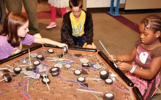 Three children building model Mars rovers out of K'nex in the Space Command exhibit at The Franklin Institute.
