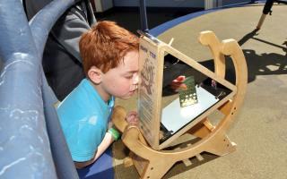A young boy looking through the sunspotter telescope in The Franklin Institute's Observatory.