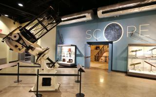View of Scope Lobby, displaying antique microscopes and telescopes.
