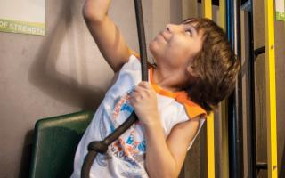 A boy lifting himself on an interactive in Sir Issac's Loft at The Franklin Institute.