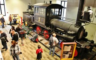 Photo of visitors playing around a train in the train factory exhibit